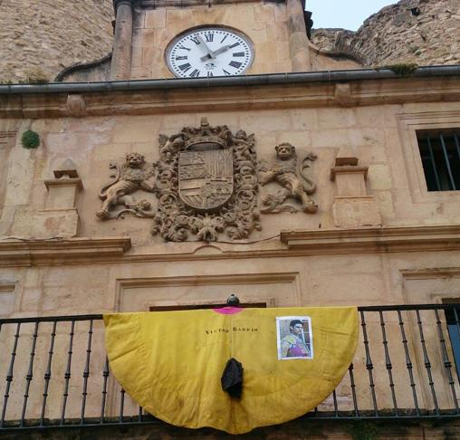 El capote de Víctor Barrio colgado en el balcón de la casa del reloj, con un crespón negro