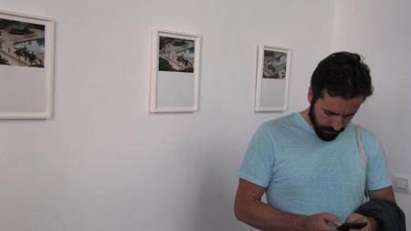 Un joven consulta el móvil frente a las fotos de Gustav Cramer