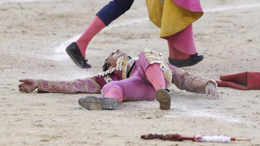 Tulio Salguero, caído en la arena tras la cornada, de pronóstico menos grave