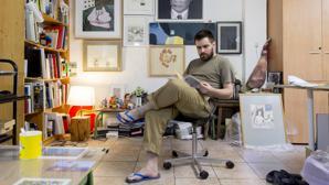 El artista lee un libro en el área de descanso de su taller