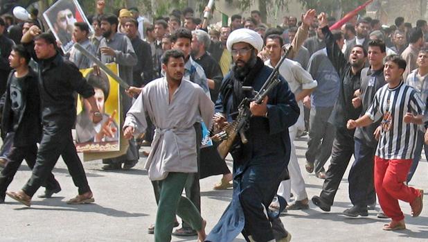 Foto de archivo de una multitud de manifestantes, entre ellos miembros del Ejército de Mehdi, una milicia iraquí prohibida que apoya al clérigo radical anti-estadounidense Moqtada al Sáder, marcha sobre una guarnición española en Nayaf en 2004
