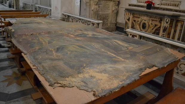 Una de las pinturas seriamente dañada se seca encima de unos bancos