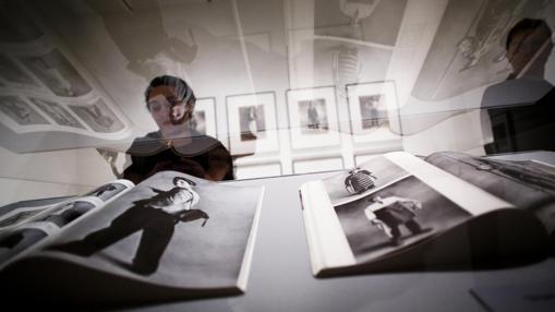 Una mujer observa varias fotografías de la muestra