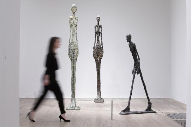 Una mujer pasea ante varias esculturas de Giacometti