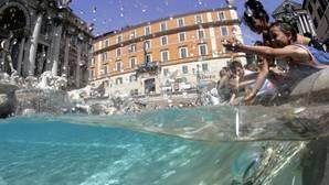 Varios niños juegan en la Fontana di Trevi, en Roma