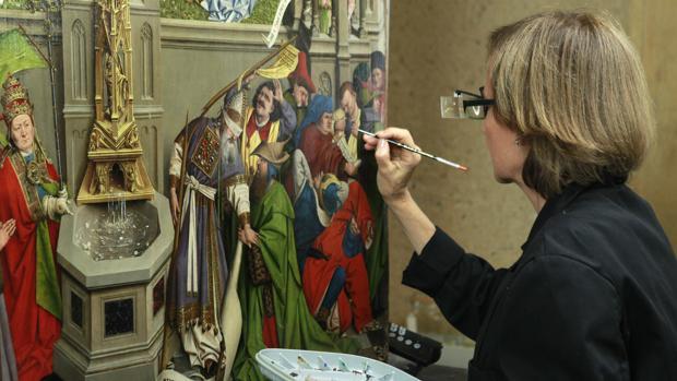 Una restauradora del Prado trabaja en el cuadro atribuido al taller de Jan van Eyck «La Fuente de la Gracia» en el taller de Restauración de la pinacoteca, que hoy ha abierto sus puertas con motivo de la presentación de su próxima Cátedra