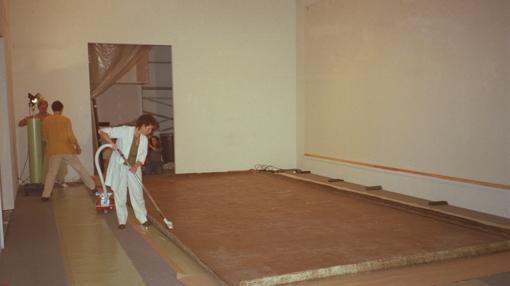 Anny Aviram se afana en eliminar, con una aspiradora, el polvo acumulado en algunas zonas del reverso del cuadro