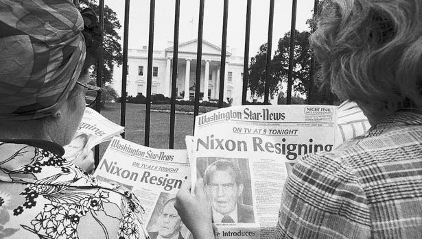 Unas turistas frente a la Casa Blanca leen los titulares de prensa del 8 de agosto de 1974 que anuncian la inminente dimisión de Richard Nixon