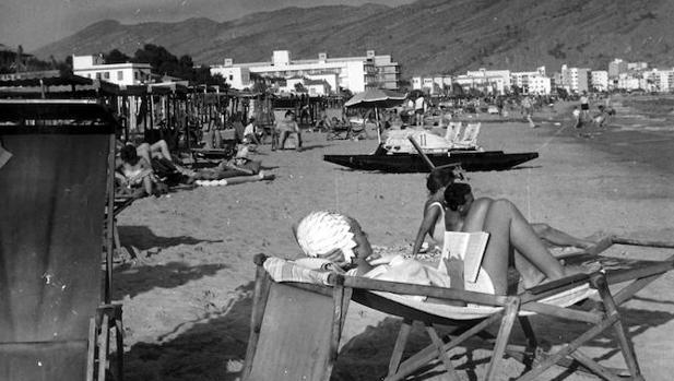 Benidorm (Alicante), septiembre de 1962. Una turista leyendo mientras toma el sol en la playa