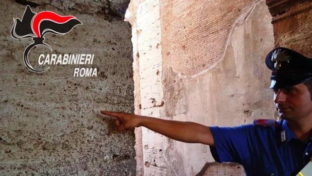 Un carabinieri señala las letras pintadas sobre el mármol travertino original