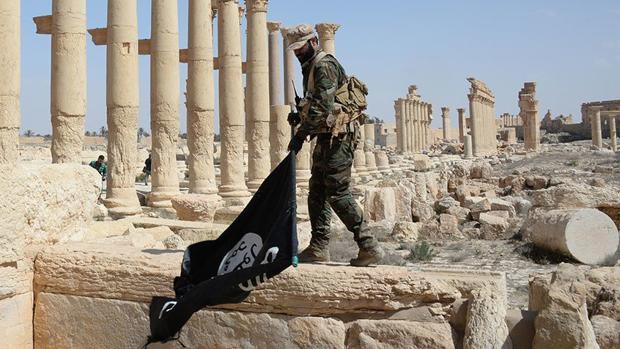 Un soldado sirio quita una bandera del «califato» en las ruinas de Palmira