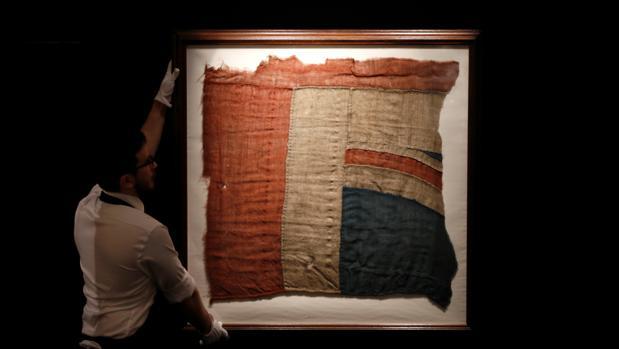 Un empleado de Sotheby's muestra el fragmento de la bandera que Nelson ondeó en Trafalgar