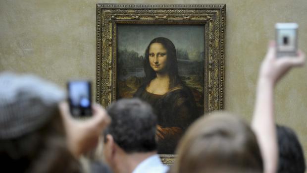 Un grupo de turistas fotografía la «Gioconda» en el Museo del Louvre, en París