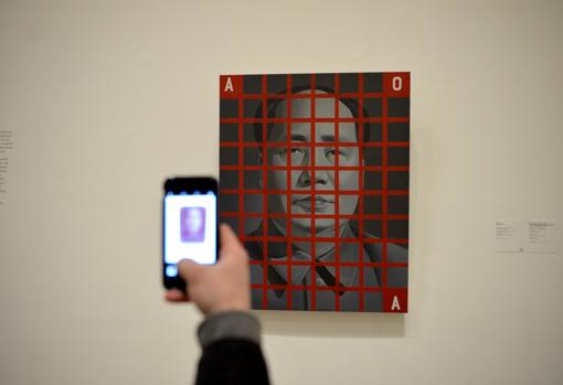 Un visitante hace una foto con su móvil a «Mao Zedong: cuadrícula roja nº 2», de Wang Guangyi