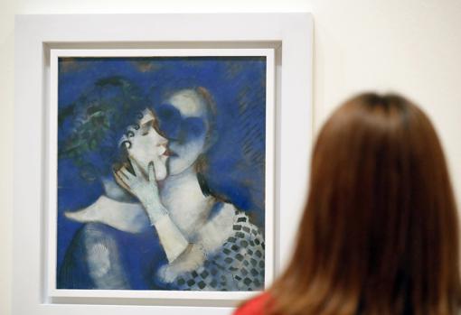 Una mujer admira «Amantes en azul» (1914), de Marc Chagall