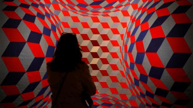 Una mujer admira una obra presente en la muestra
