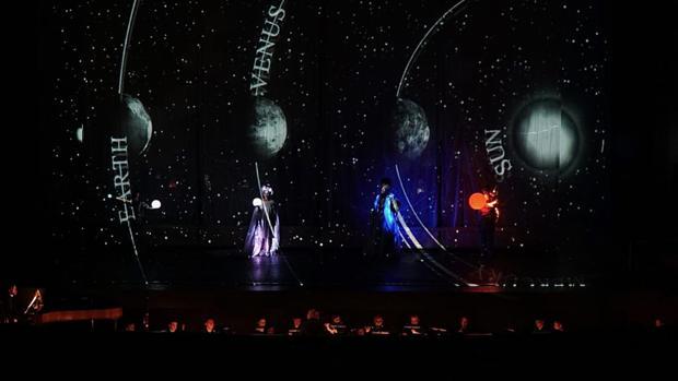 Una escena de la ópera donde incluyen figuras de planetas
