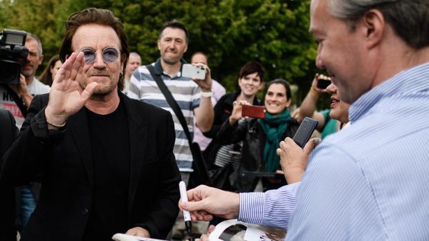 Bono, líder de U2, atiende a sus fans poco después de reunirse con la canciller alemana Angela Merkel en Berlín