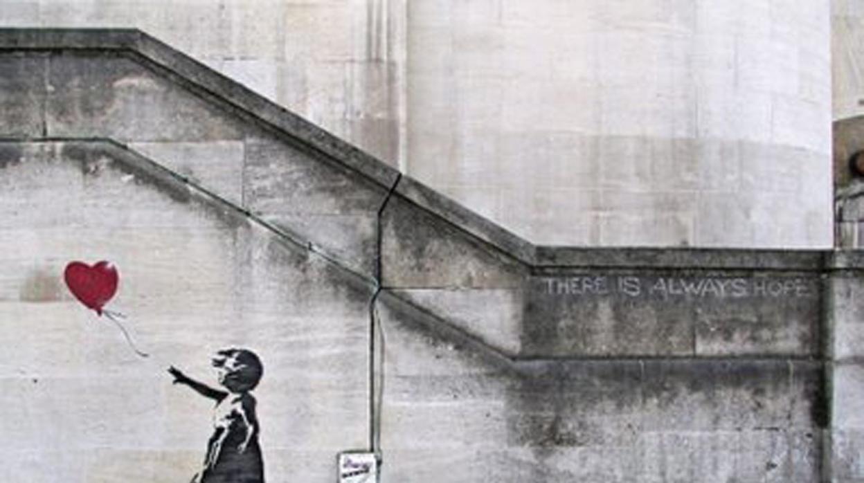 Un pintor de brocha gorda pinta encima de uno de los primeros graffitis de Banksy