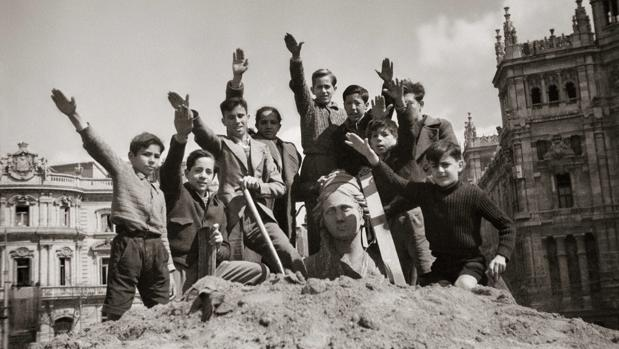 Niños saludando con el brazo en alto durante el desescombro de la Cibeles en 1939