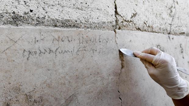 Una arqueóloga señala la inscripción encontrada en una domus de Pompeya