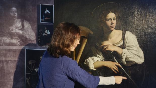 La restauradora Susana Pérez señala un detalle del lienzo. A la izquierda, la radiografía