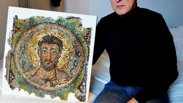 El detective de arte holandés Arthur Brand posa con el mosaico recuperado