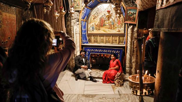 Una pareja se fotografía ante la Gruta de la Basílica de la Natividad, en Belén