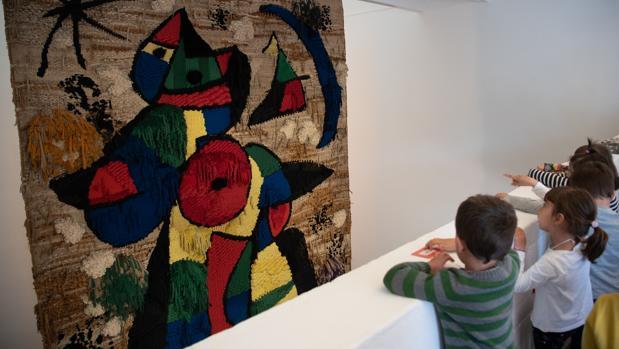 Un grupo de estudiantes observa el tapiz de Miró