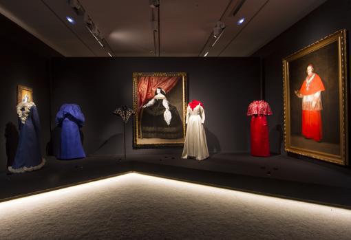 En el centro de la imagen, en blanco y rojo, el Vestido Infanta de Balenciaga, junto a una obra de Carreño de Miranda