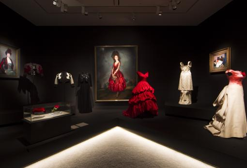 En el centro de la imagen, «Retrato de la Duquesa de Alba», de Ignacio Zuloaga, junto con un vestido de noche rojo de Balenciaga