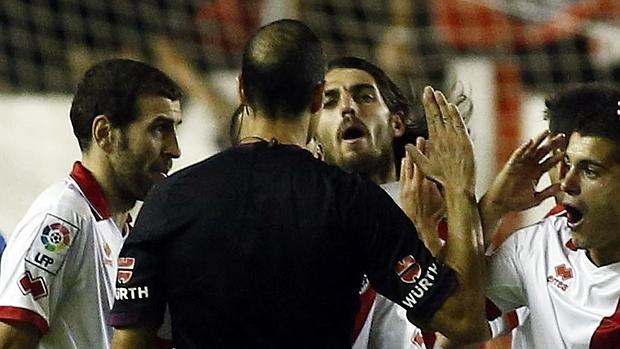 Un árbitro rodeado por jugadores que le protestan