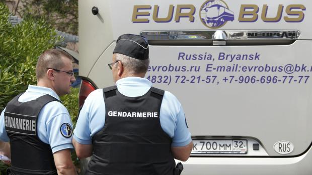 Policías franceses, junto a un autobús de aficionados rusos