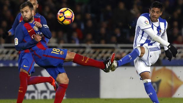 Jordi Alba intenta cortar un disparo de Carlos Vela en el partido que el Barcelona jugó ante la Real Sociedad