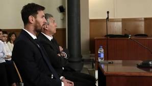 Leo Messi y su padre Jorge sentandos en el banquillo este pasado año