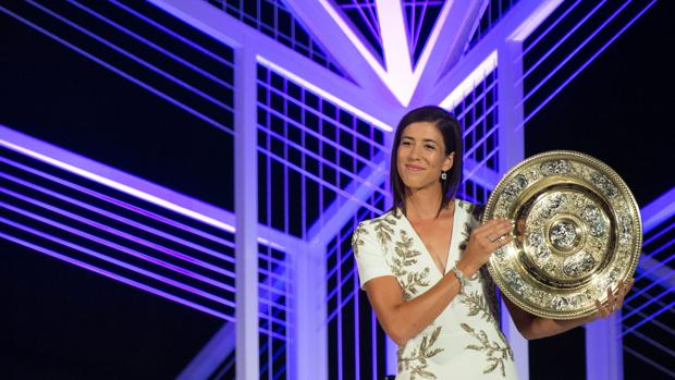 Muguruza posa sonriente con su trofeo durante la cena de gala a los campeones de Wimbledon