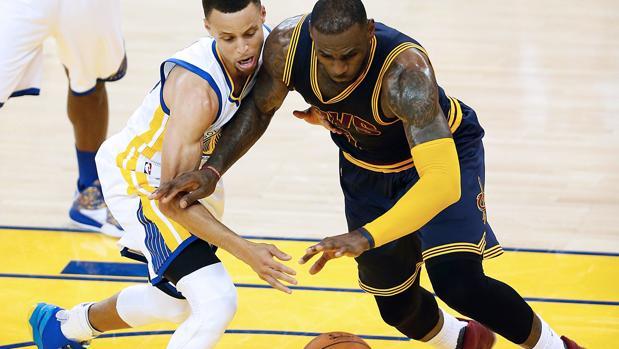 Stephen Curry (Warriors) pelea por el balón con LeBron James (Cavaliers)