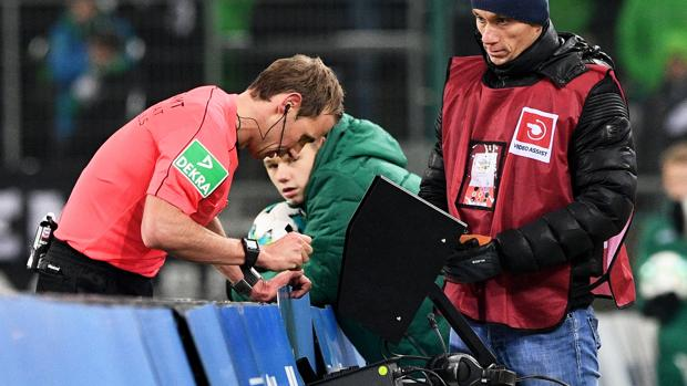 Un árbitro revisa un vídeo durante un partido de la Bundesliga
