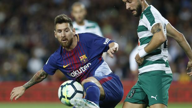 Leo Messi y David Junca pelean un balón
