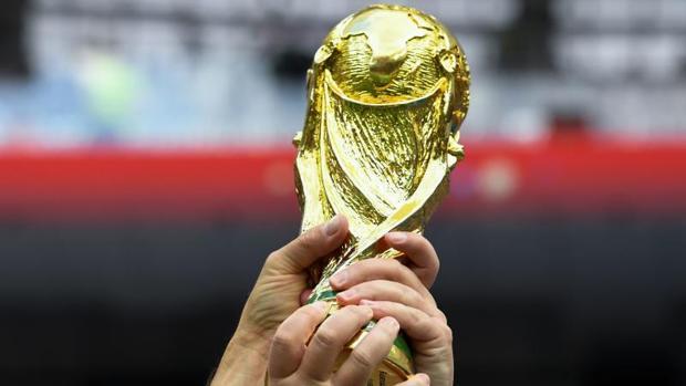 Unos aficionados ingleses sostienen una réplica de la copa del mundo