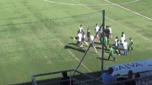 El niño lesionado es retirado del campo por el delegado de su equipo