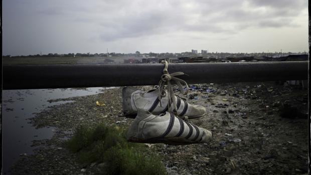 Unas viejas botas de fútbol, colgadas en un puente en Agbogbloshie (Ghana)