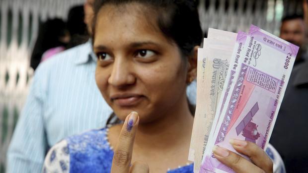 Una mujer muestra su dedo teñido con tinta permanente después de cambiar por otros nuevos los billetes retirados de la circulación la semana pasada, en una sucursal bancaria en Bhopal, en la India