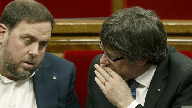 El presidente de la Generalitat de Cataluña, Carles Puigdemont,d., conversa con el vicepresidente, Oriol Junqueras (i)