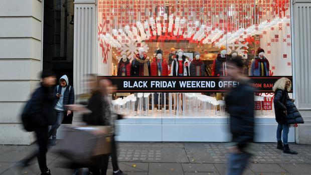 Fotografía de archivo de peatones pasando junto a los escaparates de tiendas que exponen sus descuentos por el Black Friday
