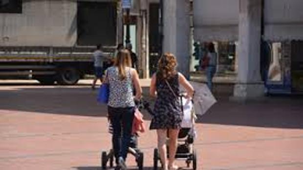 Dos jóvenes pasean a sus bebés