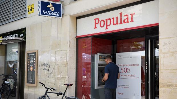 Las oficinas del Popular y el Pastor siguen luciendo sus marcas y un añadido con el logo del grupo Santander