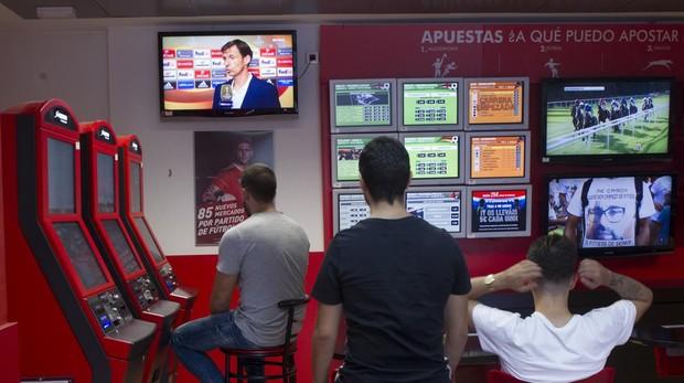 Jóvenes viendo un partido de fútbol en una casa de apuestas de Alcorcón (Madrid)