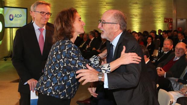 La ministra Teresa Ribera saluda al presidente de Repsol, Antonio Brufau, con el presidente de BP, Luis Aires, como testigo, al comienzo del acto