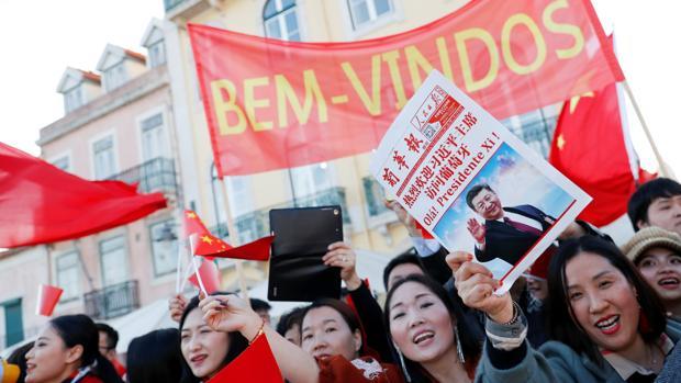 Un grupo de jóvenes saluda a la comitiva de Xi Jinping en las calles de Lisboa